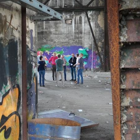 Auf diesem Bild sehen Sie eine Gruppe CDU-Ratsmitglieder aus einiger Entfernung in einer ehemaligen Werkshalle stehen.