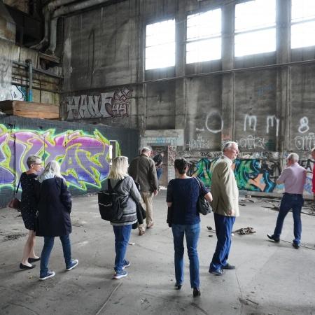 Auf diesem Bild sehen Sie CDU-Ratsmitglieder, die eine ehemalige Werkshalle verlassen.