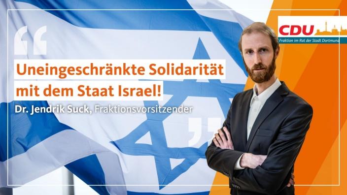 Auf diesem Bild sehen Sie den Fraktionsvorsitzenden Dr. Jendrik Suck vor einer Israel-Flagge.
